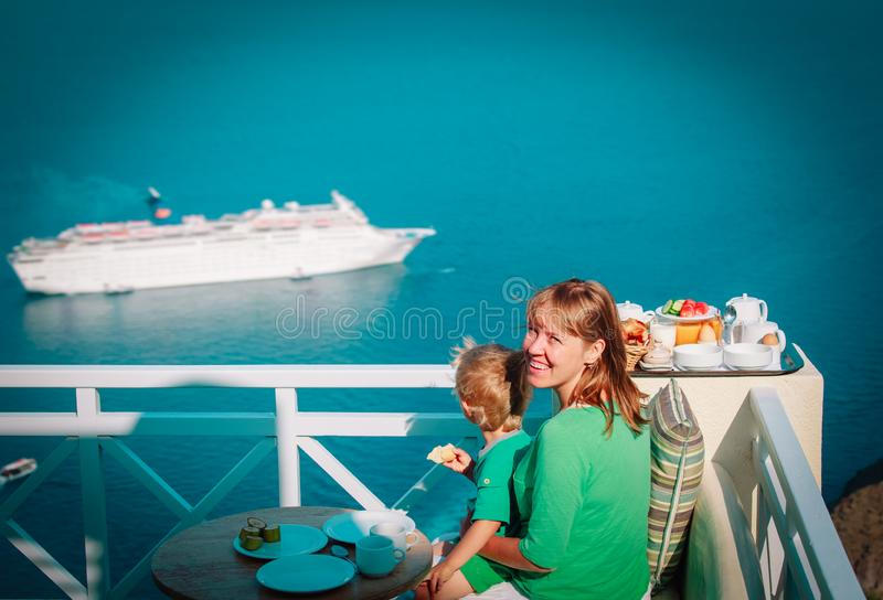 Happy mother and little son looking at cruise ship at sea, having breakfast stock photography