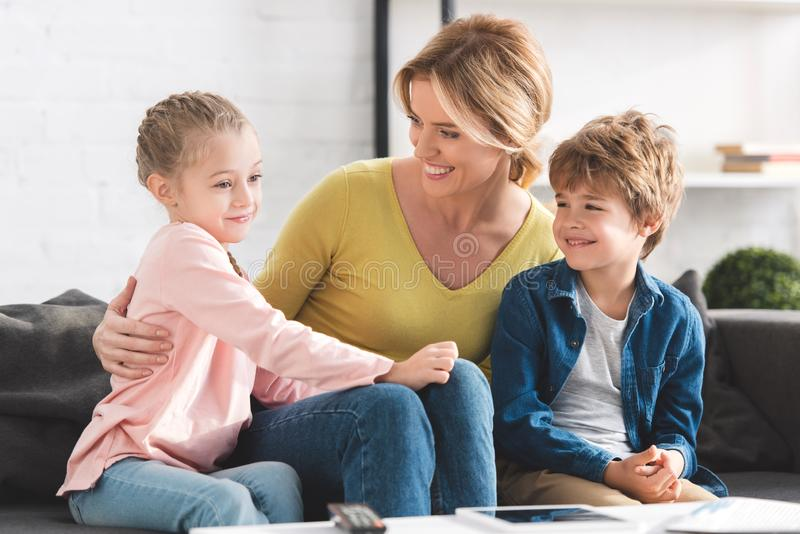 happy mother looking at adorable smiling children sitting together royalty free stock image