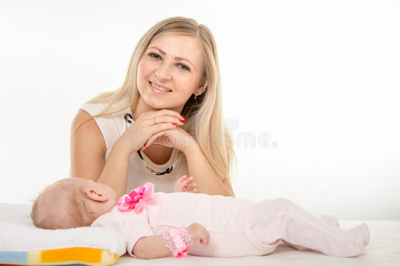 Happy mother looking into the frame next to it is a two-month daughter. A two-month baby lying on his back on the bed, sitting next to the child and mother royalty free stock image