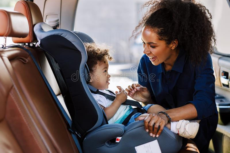 Happy mother looking at her son in a baby seat royalty free stock image