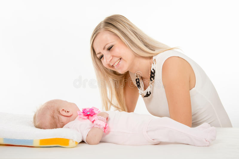 Happy mother looking at a two-month daughter. A two-month baby lying on his back on the bed, sitting next to the child and mother looking at her royalty free stock image