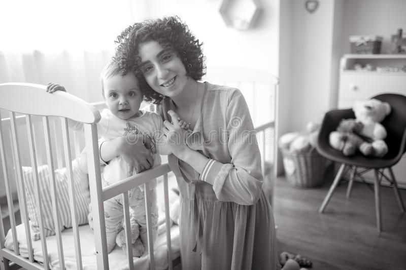 Happy mother is next her baby in the crib. Black and white image stock photo