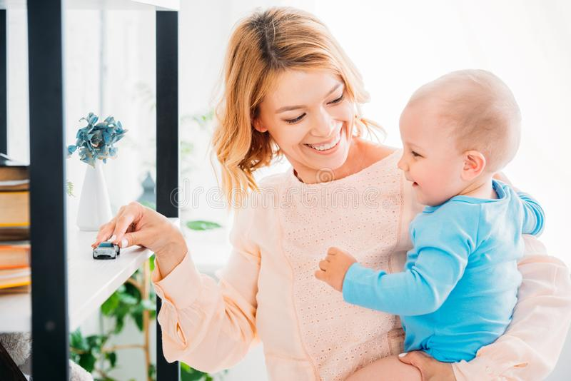 Happy mother playing with child and riding toy car. On bookshelf stock image