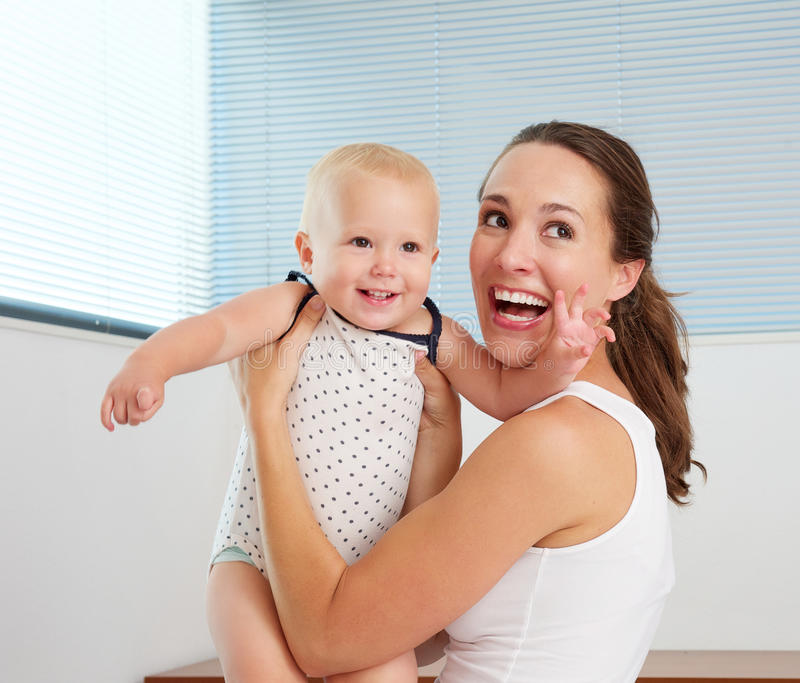 Download Happy Mother Playing With Cute Smiling Baby At Home Stock Photo - Image: 34073568