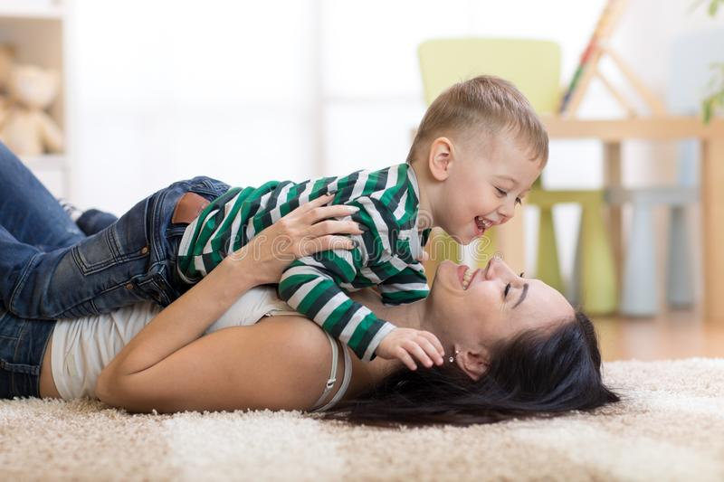 Happy mother playing with kid on floor in children room royalty free stock photos