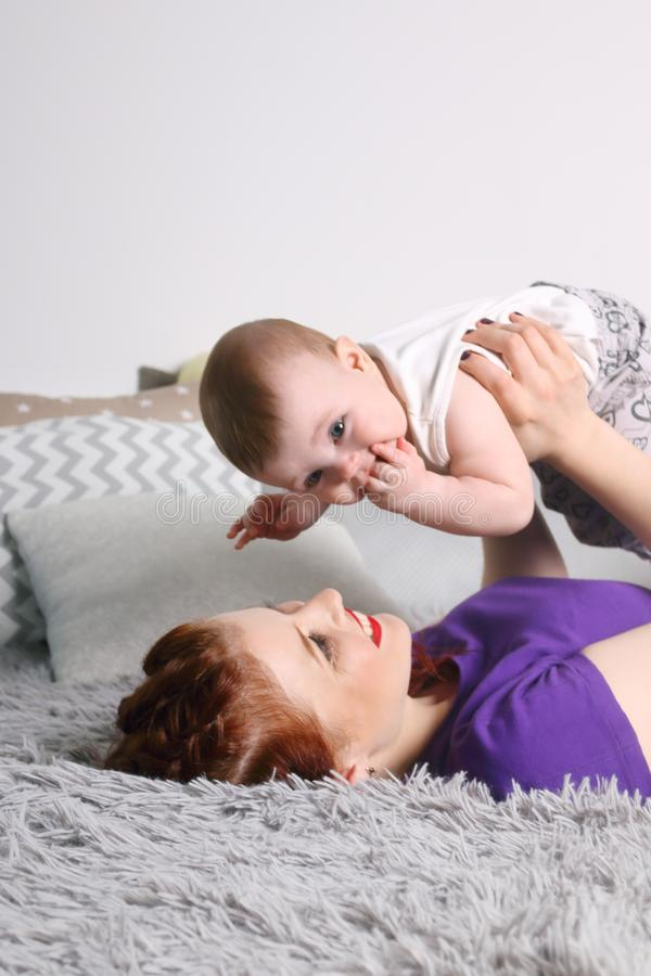Happy mother plays with her little baby on bed stock image