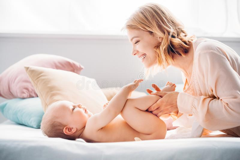 Happy mother putting diaper on little child. On bed royalty free stock images