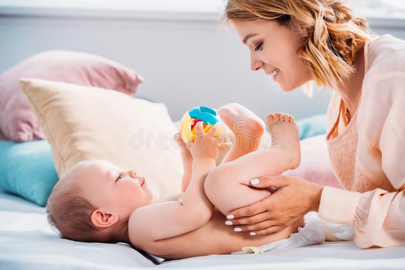 Happy mother putting diaper on little child. While he playing with toy stock photos