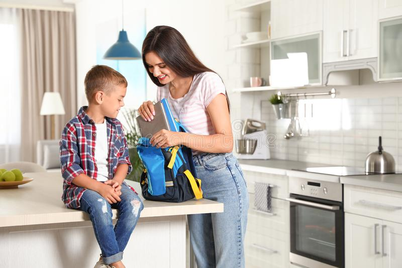 Happy mother putting textbooks into little child`s school bag. In kitchen royalty free stock photography