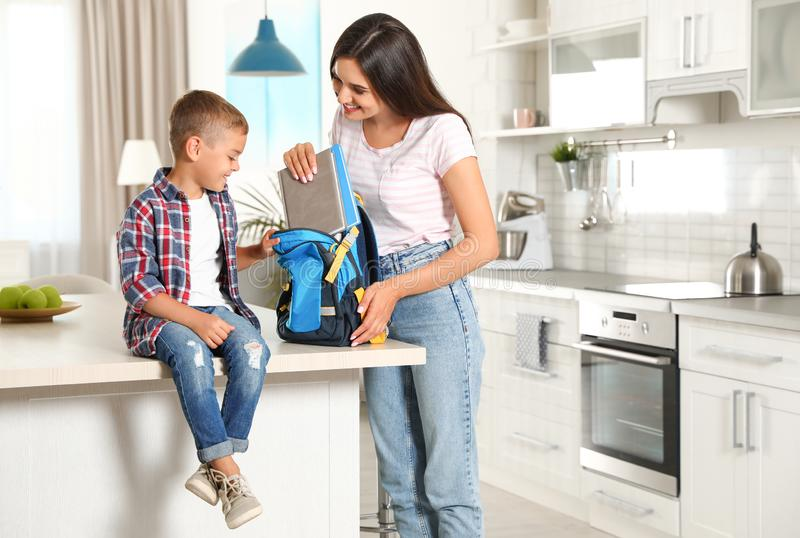 Happy mother putting textbooks into little child`s school bag. In kitchen stock photos
