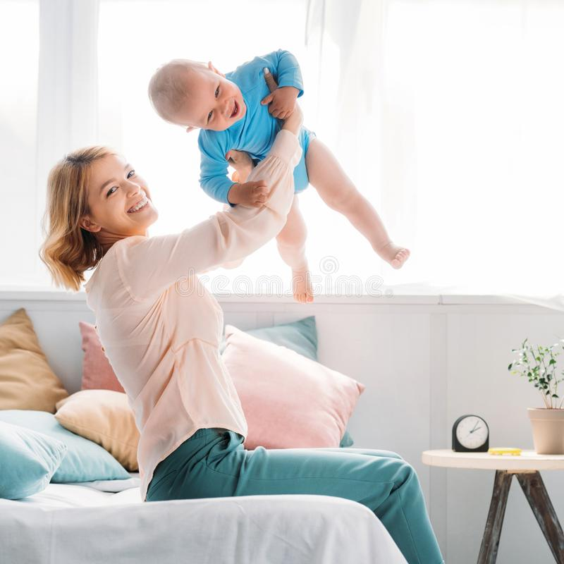 Happy mother raising up laughing little child. While sitting on bed at home royalty free stock photography