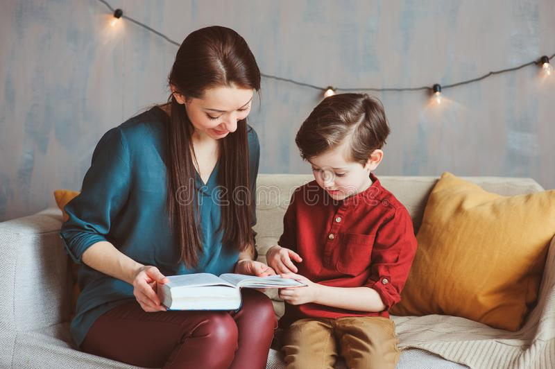 Happy mother reading book to child son at home, learning toddlers to read, stock photography