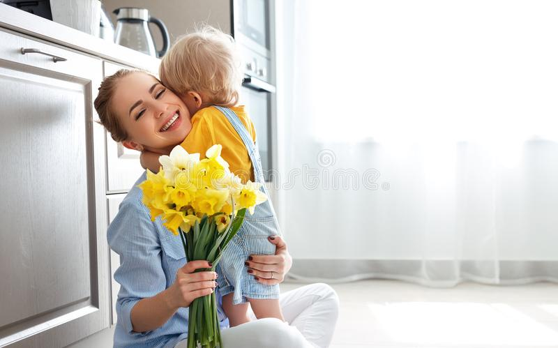 Happy mother`s day! baby son gives flowersfor mother on holiday. Happy mother`s day! baby son congratulates mother on holiday and gives flowers stock photos