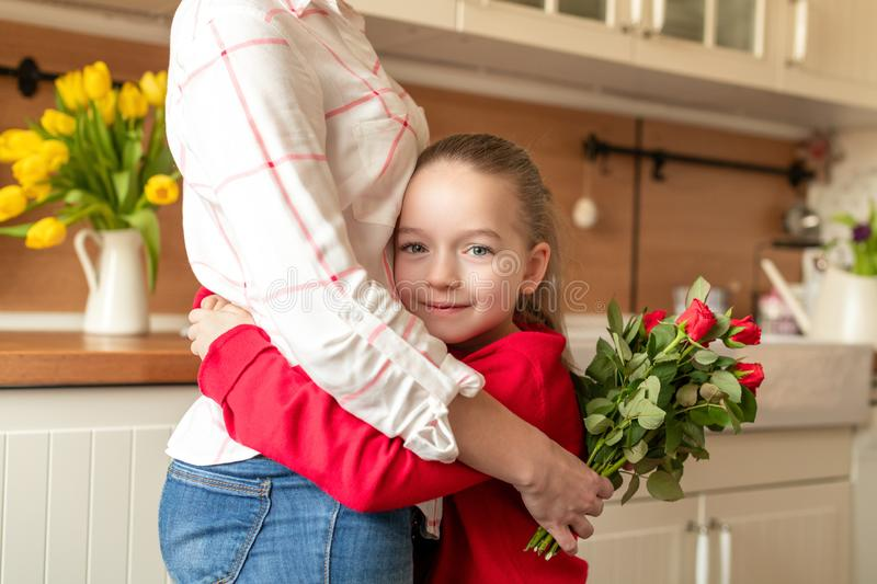 Happy Mother`s Day or Birthday Background. Adorable young girl hugging her mom after surprising her with bouquet of red roses. royalty free stock images