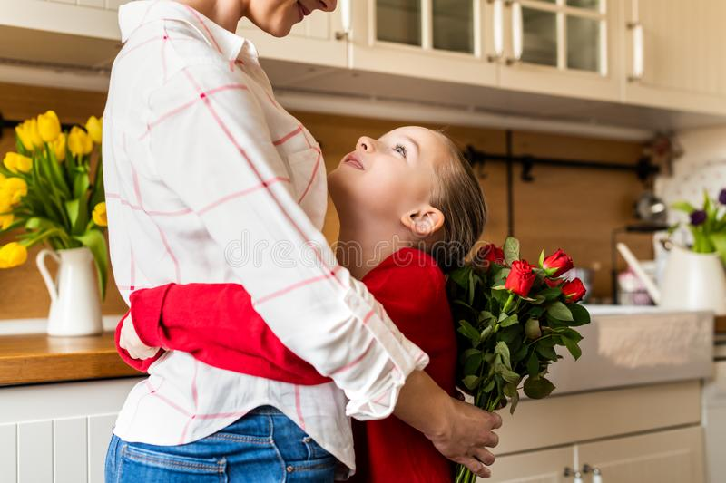 Happy Mother`s Day or Birthday Background. Adorable young girl hugging her mom after surprising her with bouquet of red roses. stock image