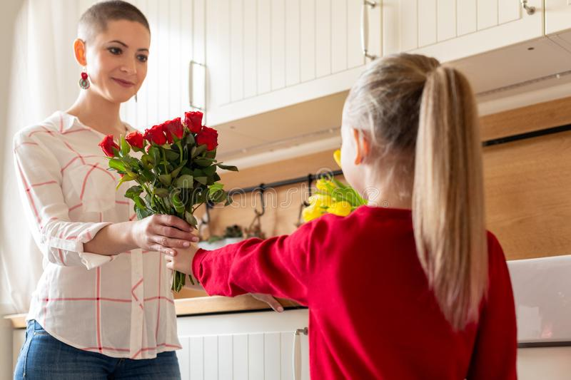 Happy Mother`s Day or Birthday Background. Adorable young girl surprising her mom with bouquet of red roses. Family celebration. royalty free stock photos