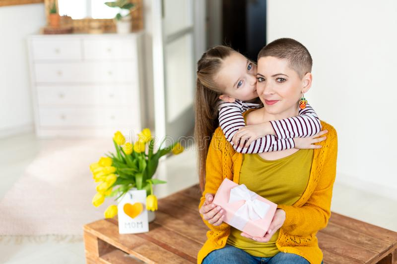 Happy Mother`s Day or Birthday Background. Adorable young girl surprising her mom, young cancer patient, with bouquet and present. Family celebration concept stock images