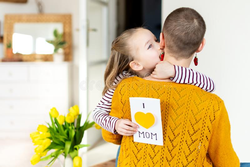 Happy Mother`s Day or Birthday Background. Adorable young girl surprising her mom, young cancer patient, with bouquet and present. royalty free stock images