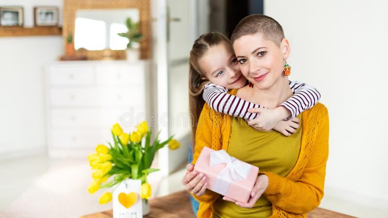 Happy Mother`s Day or Birthday Background. Adorable young girl surprising her mom, young cancer patient, with bouquet and present. Family celebration concept royalty free stock photos