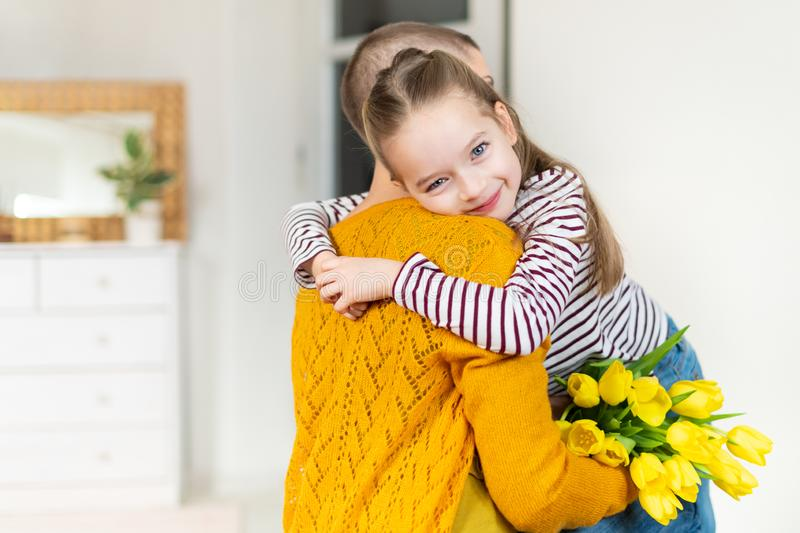 Happy Mother`s Day or Birthday Background. Adorable young girl surprising her mom, young cancer patient, with bouquet of tulips. royalty free stock photo