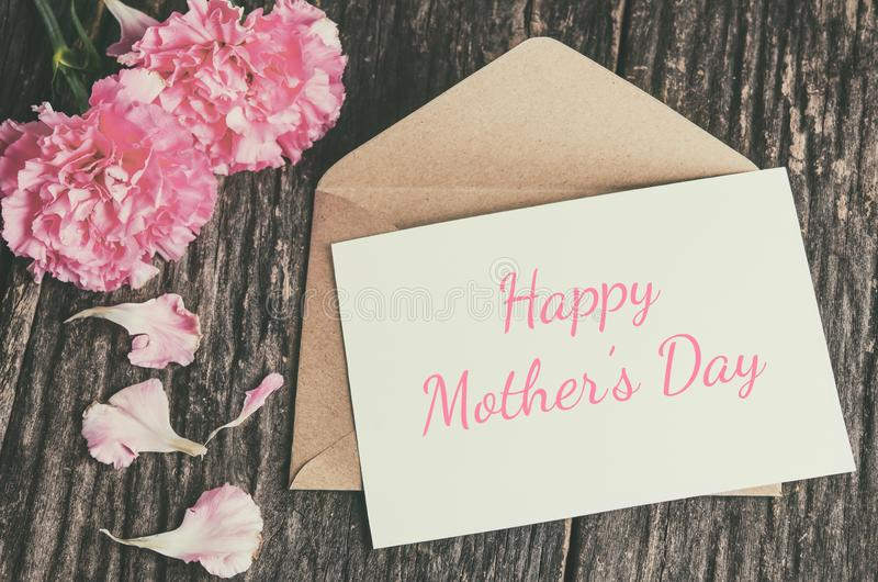 Happy Mother`s Day card with brown envelope and pink carnation f royalty free stock photos