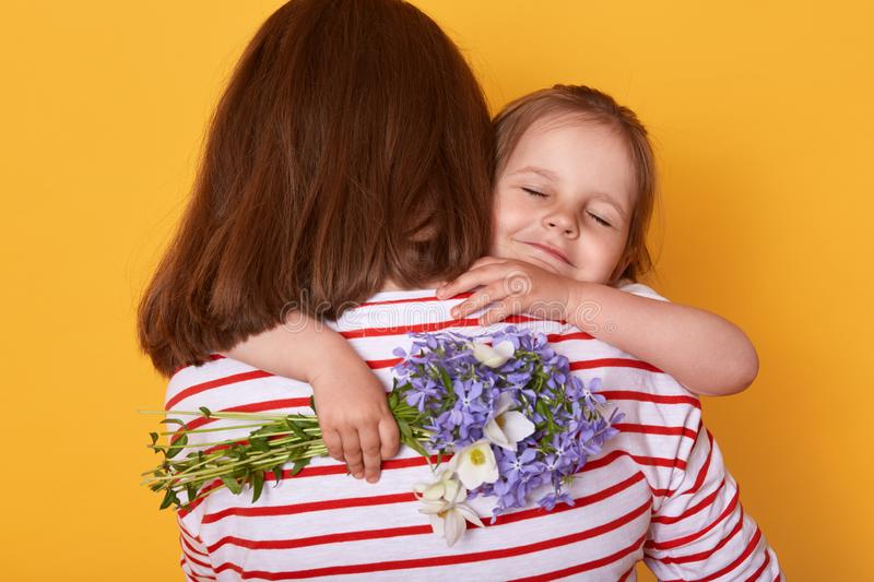 Happy Mother`s day! Child daughter congratulates mom and gives her flowers. Mum and little girl hugging, charming kid closes eyes stock photography