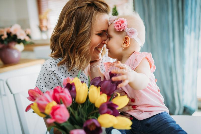 Child daughter congratulates moms and gives her flowers royalty free stock photos