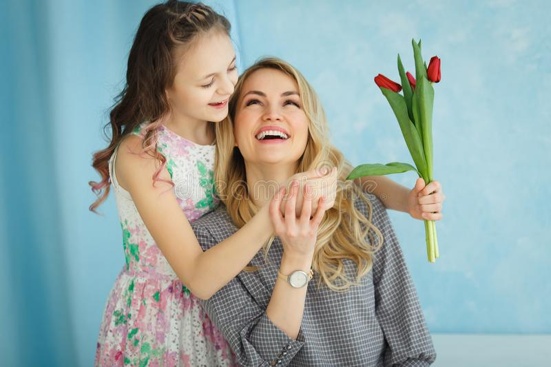 Happy mother`s day. Child daughter congratulates moms and gives her a postcard and flowers tulips. royalty free stock image