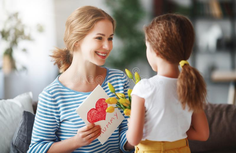 Happy mother`s day! Child daughter congratulates moms and gives her a postcard and yellow flowers tulip stock photo