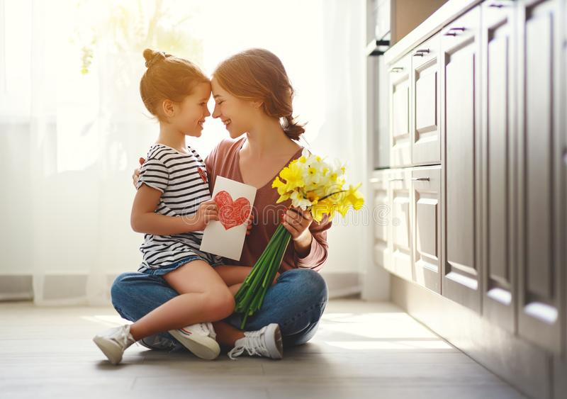 Happy mother`s day! child daughter   gives mother a bouquet of flowers to narcissus and gift royalty free stock photos