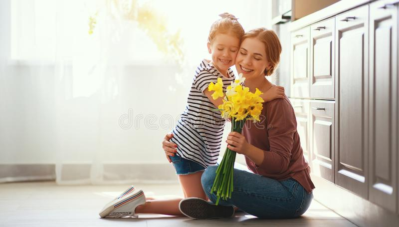 Happy mother`s day! child daughter   gives mother a bouquet of flowers to narcissus and gift royalty free stock photography