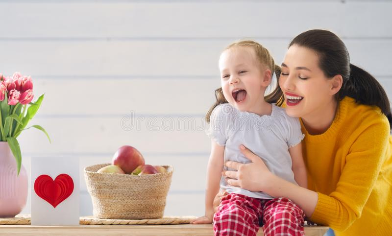 Happy mother`s day. ! Child daughter is congratulating mom and giving her card. Mum and girl smiling. Family holiday and togetherness stock photos