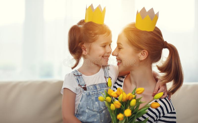 Happy mother`s day! mother and child daughter in crowns and with. Flowers yellow tulips stock photography