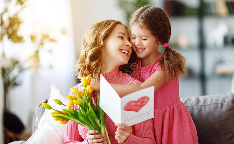 Happy mother`s day! child daughter gives mother a bouquet of flowers to tulips and postcard stock images