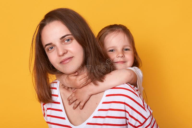 Happy mother`s day! Child daughter hugging mom from behind. Mum wearing striped shirt and little girl looking at camera with happ royalty free stock images