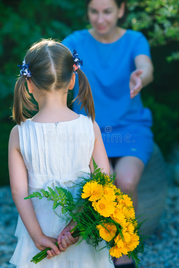 Happy mother`s day! Child girl congratulates mom and gives her b royalty free stock image