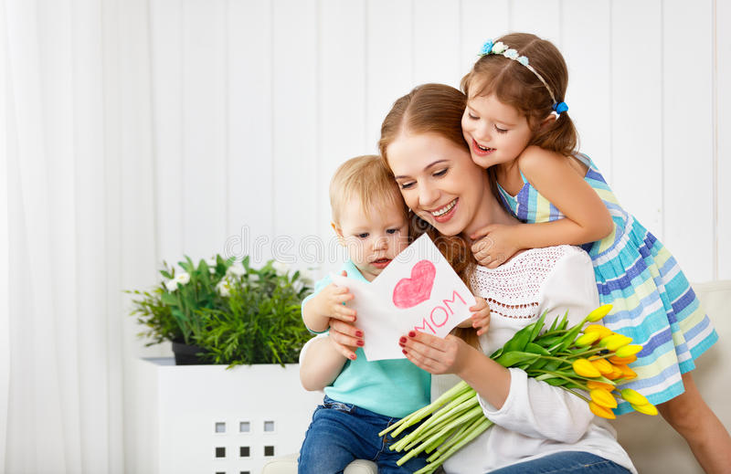Happy mother`s day! Children congratulates moms and gives her a royalty free stock photography