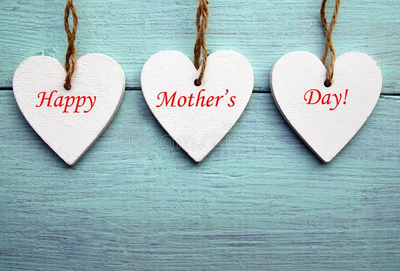 Happy Mother`s Day concept.Decorative white wooden hearts on a blue rustic wooden background. stock photos