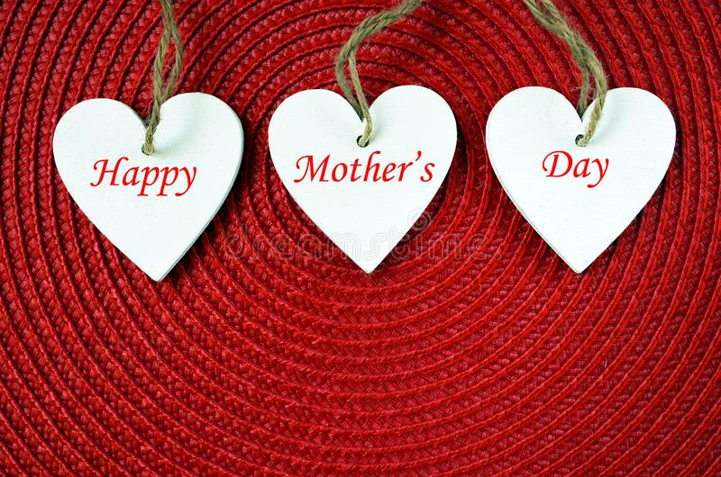 Happy Mother`s Day concept.Decorative white wooden hearts on a red straw background. stock photos