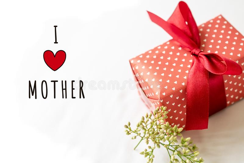 Happy Mother`s day concept. Gift box and flower, paper tag with I LOVE MOTHER text stock photo