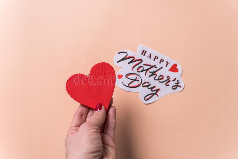 Happy mother`s day, congratulations creative concept. Red wooden heart and Happy Mother`s Day Typographic Lettering With Heart i stock images