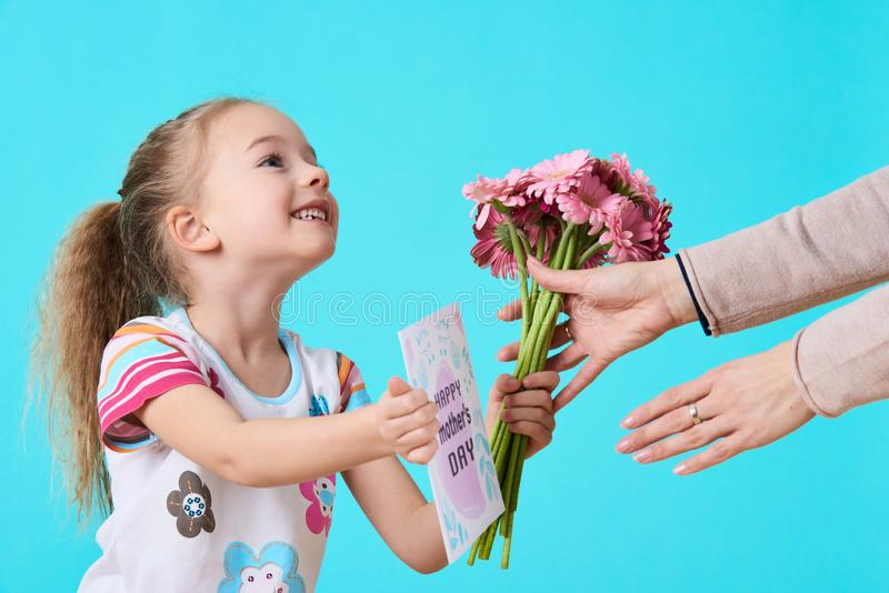 Happy Mother`s Day. Cute little girl giving mom greeting card and bouquet of pink gerbera daisies. Mother and daughter concept. stock images
