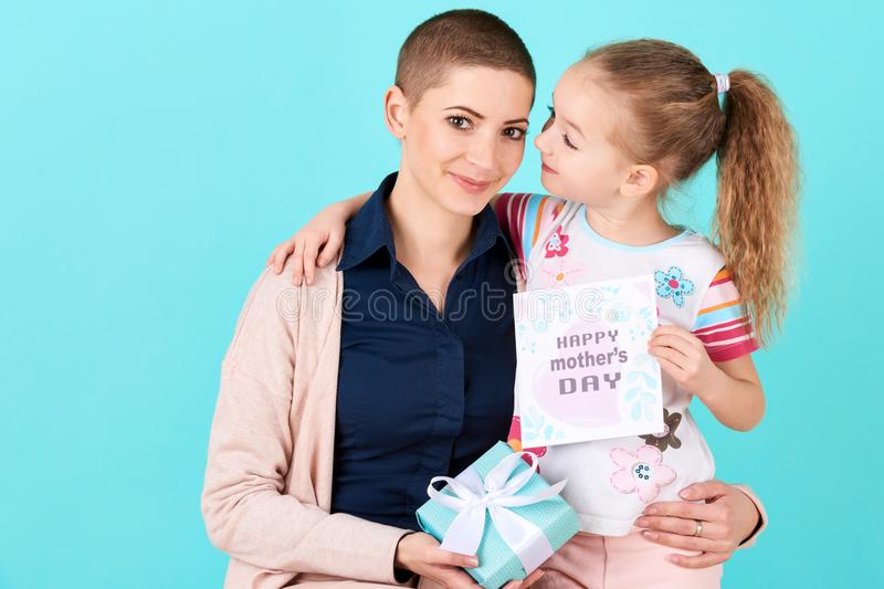 Happy Mother`s Day. Cute little girl giving mom mothers day card and a present. Mother and daughter concept. stock photo
