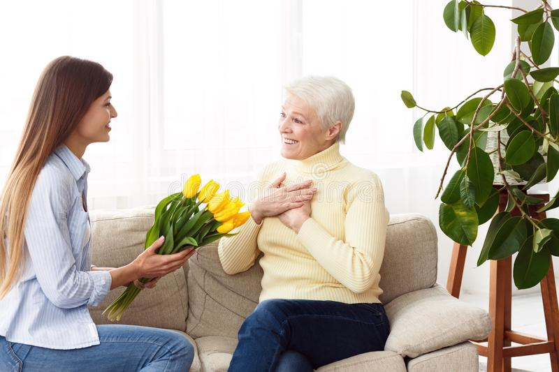 Happy mother`s day. Daughter giving bouquet to mom royalty free stock photography