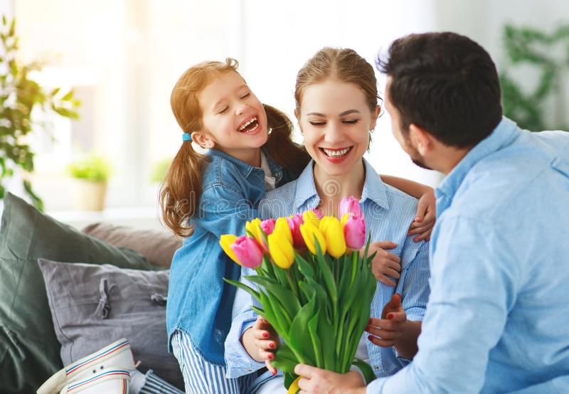 Happy mother`s day! father and child congratulate mother on holiday. Happy mother`s day! father and child daughter congratulate mother on holiday and give stock images