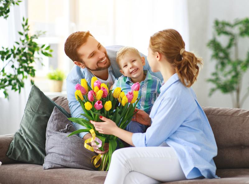 Happy mother`s day! father and child congratulate mother on holiday. Happy mother`s day! father and child son congratulate mother on holiday and give flowers stock photos
