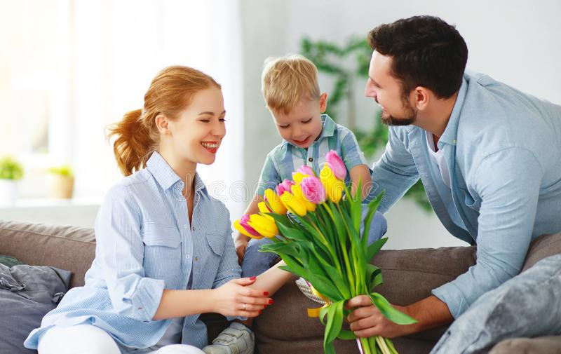 Happy mother`s day! father and child congratulate mother on holiday. Happy mother`s day! father and child son congratulate mother on holiday and give flowers royalty free stock images