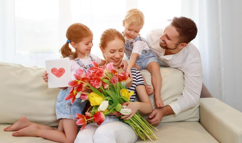 Happy mother`s day! father and children congratulate mother on h. Oliday and give flowers stock photos