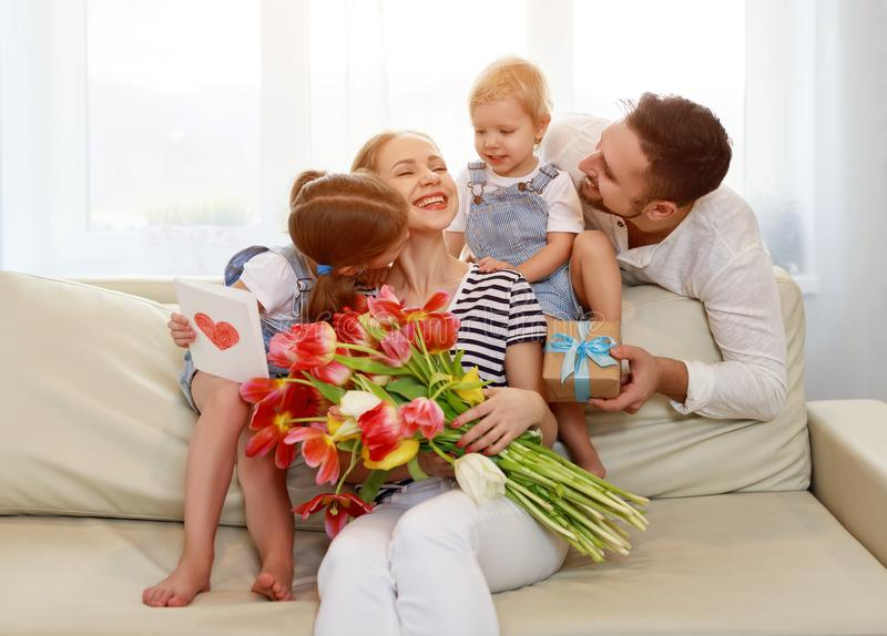 Happy mother`s day! father and children congratulate mother on h. Oliday and give flowers royalty free stock image