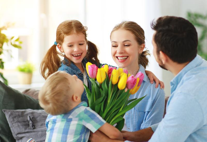 Happy mother`s day! father and children congratulate mother on holiday. And give flowers royalty free stock image